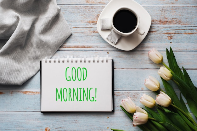 おはよう碑文とグリーティングカード。コーヒーのカップと白いチューリップの花の花束