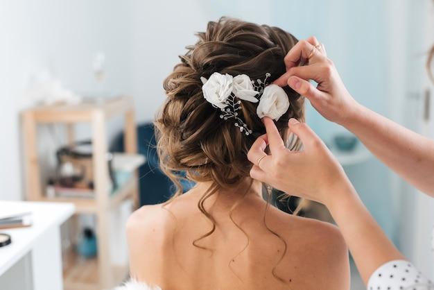 美容師は彼女の髪に白い花を持つエレガントな髪型スタイリング花嫁を作ります