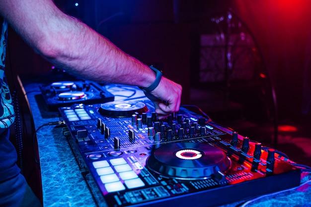 Руки диджея, играющего музыку на микшере на концерте