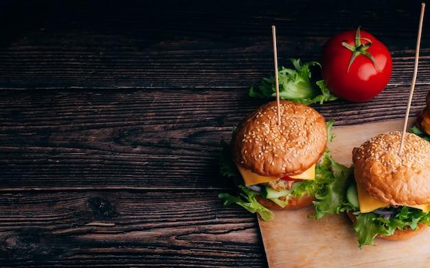 Два вкусных гамбургера с мясом, сыром, листьями салата, помидорами и луком крупным планом на деревянном фоне