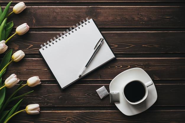 一杯のコーヒーと空のノートブックと木製のテーブルに白いチューリップ