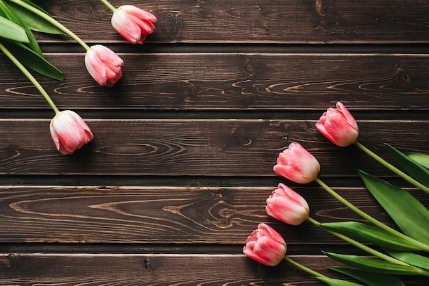 茶色の木製のテーブルにピンクのチューリップの花の花束。