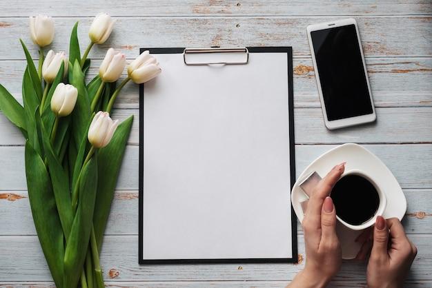 Белый букет из тюльпанов на деревянном синем столе с кофейной чашкой в женских руках