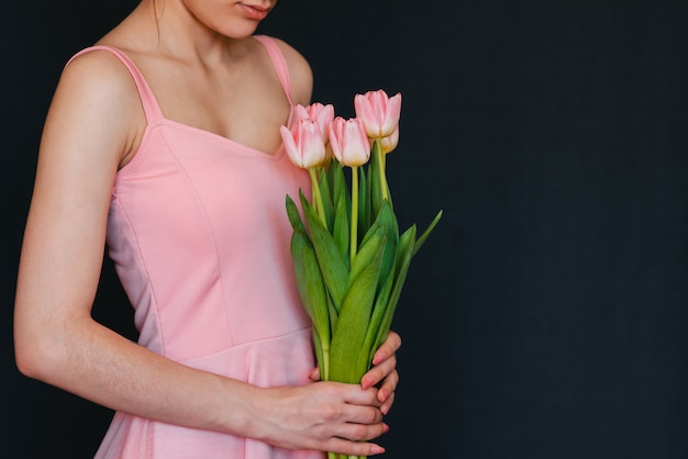 女性の手にピンクのチューリップの花束