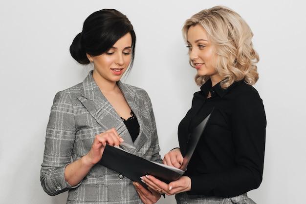 Две женщины в деловых костюмах блондинки и брюнетки-секретарши