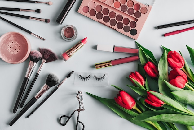 Набор косметики для макияжа и цветы красного пиона