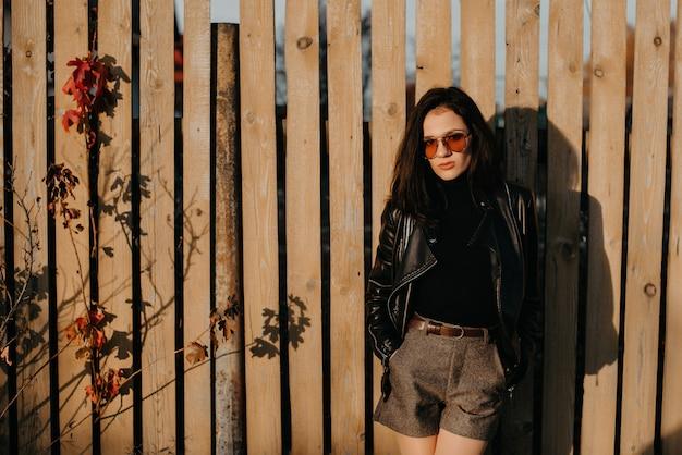 Стильная молодая брюнетка в кожаной куртке и шортах в модных солнечных очках