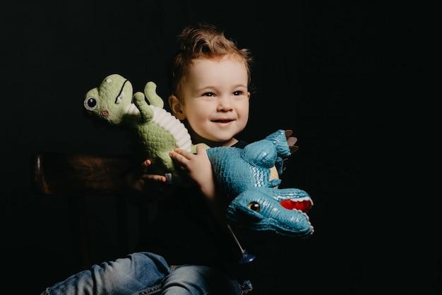 Портрет счастливого ребенка мальчик играет с игрушками динозавров