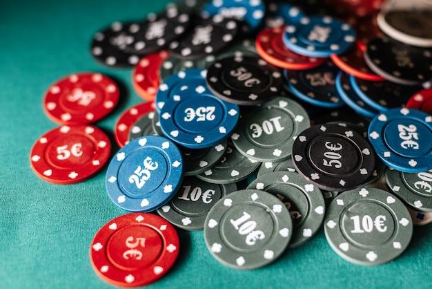 緑のテーブルの背景にカードゲームやポーカーを賭けるためのゲーミングチップ