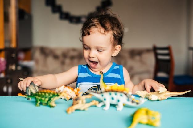 Милый мальчик играет дома с игрушечными динозаврами за столом