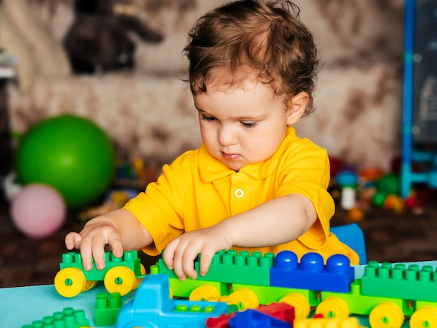 Маленький мальчик играет с пластиковыми блоками