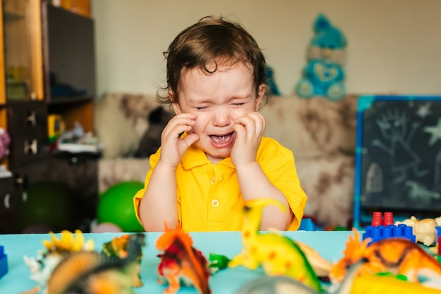 Грустный мальчик плачет рядом с игрушечными динозаврами