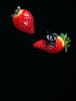 Две красные спелые клубники в шоколаде на черном фоне падения