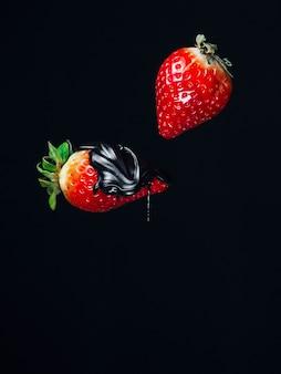 Две красные свежие сочные клубника в шоколаде на черном фоне падают летать