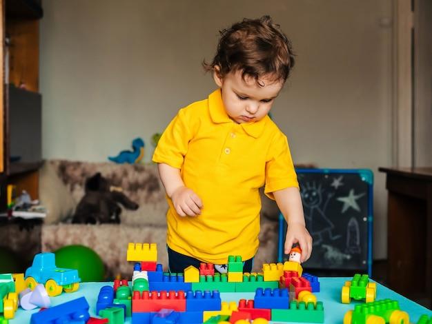 Мальчик учится строить дом из блоков