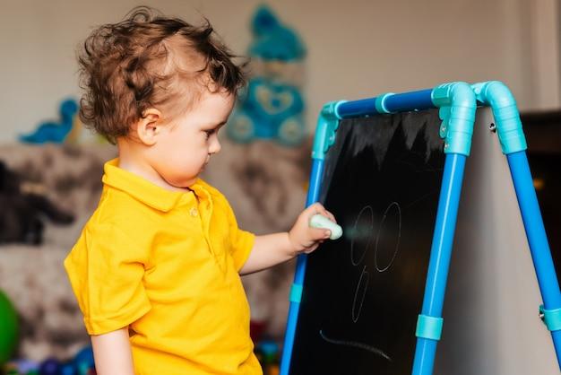 黒板にチョークで描くことを学ぶかわいい男の子