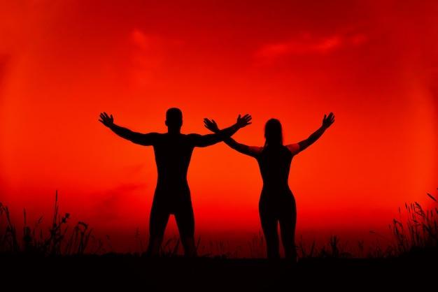 スポーティなカップルが一緒にスポーツトレーニングや自然の中でヨガの瞑想を行う
