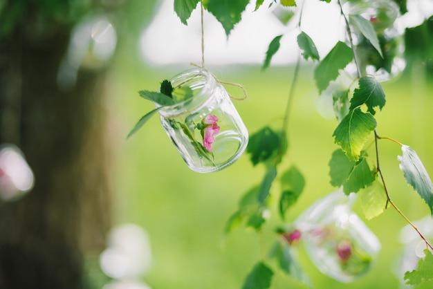 木のクローズアップにぶら下がっている花と瓶からの装飾
