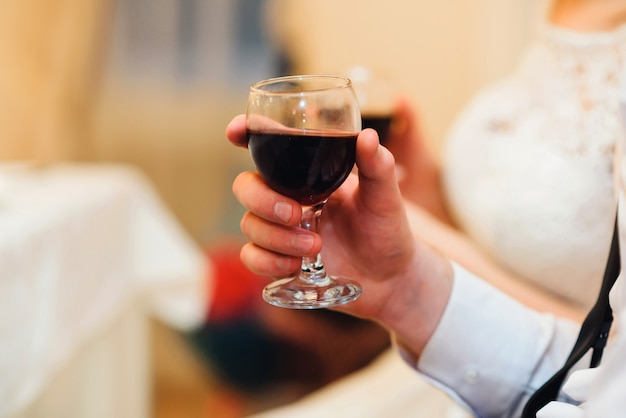Стакан красного вина в руке человека крупным планом