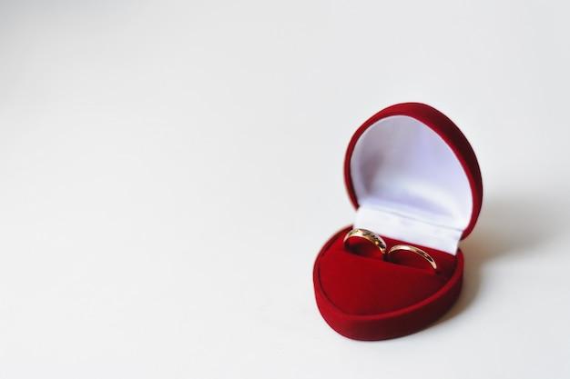 Золотые обручальные кольца в красной коробке