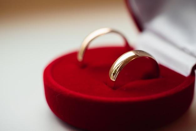 金の結婚指輪のペアは赤いボックスに横たわるをクローズアップ