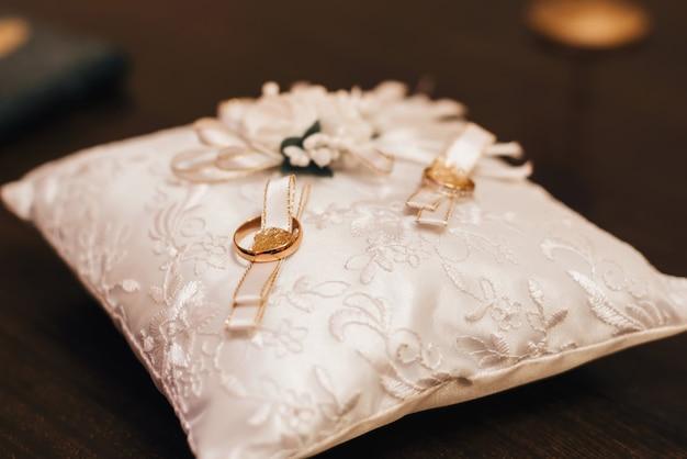 Два обручальных золотых кольца жениха и невесты для помолвки лежат на украшенной подушке