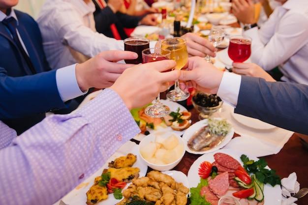 人々のグループがレストランでワインのグラスをチャリンという音します。