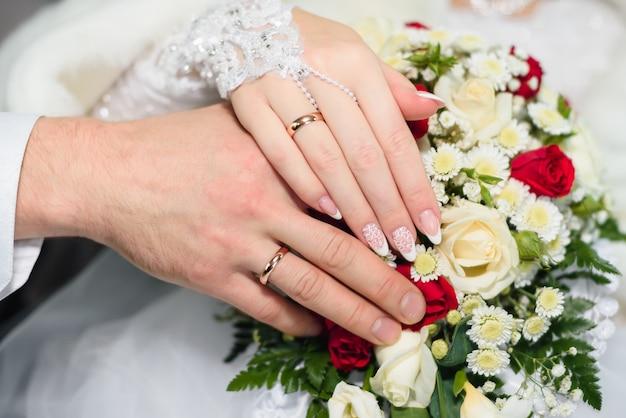 美しいブーケの金の結婚指輪と新郎新婦の手