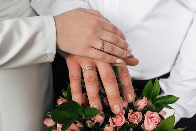 ウェディングブーケの金の指輪と新郎新婦の手