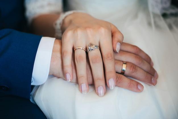 Руки жениха и невесты с золотыми обручальными кольцами на белом фоне платья