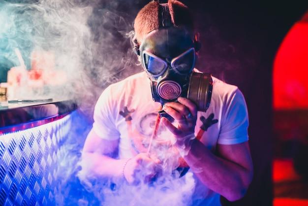 Мужчина в противогазе курит кальян и выдувает дым
