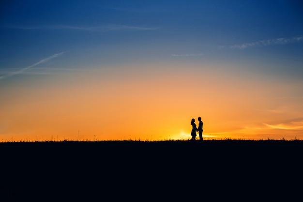 Силуэт влюбленная пара на фоне оранжевого заката летом