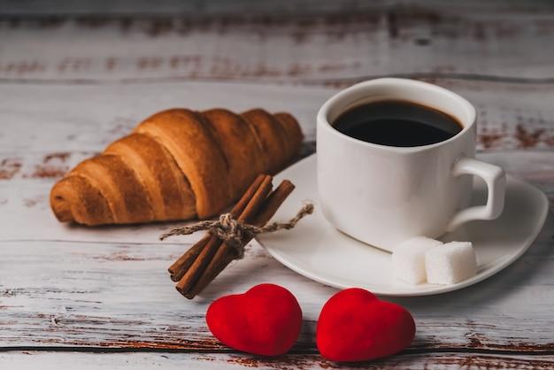 Утренний завтрак в день святого валентина, чашка кофе, круассан и пара красных сердечек