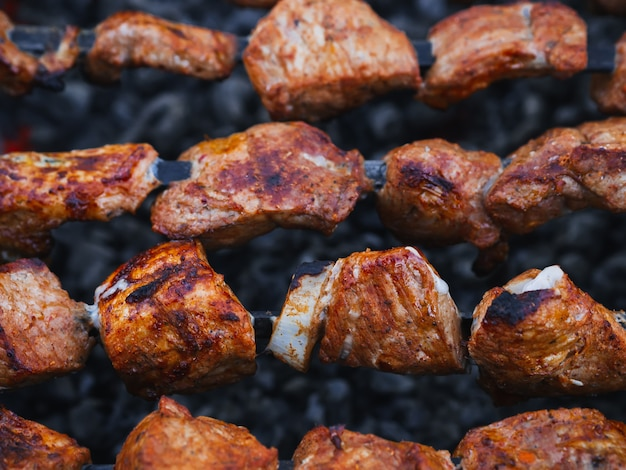 Мясо свинины готовится на шпажках на гриле