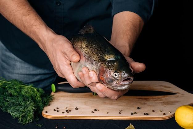 シェフの手でキッチンで大きな新鮮な魚