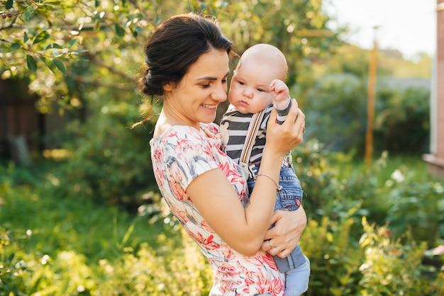 Счастливая молодая кавказская мама с мальчиком новорожденного сына в руках улыбается