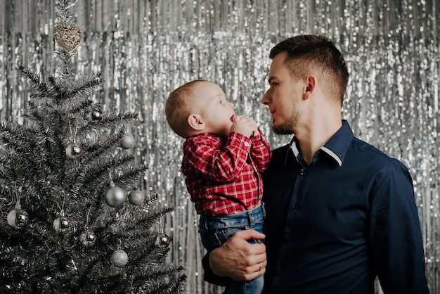 息子とパパ、クリスマスツリーで彼の父の腕の中で小さな男の子