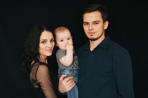 Молодая кавказская семья на черном фоне, счастливый папа, мама и сын, влюбленная пара с ребенком на руках,