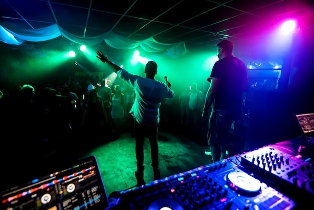 夜のクラブコンサートでダンスフロアのミュージシャンをリードする男性のシルエット