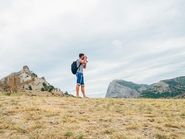 プロのカメラのバックパックで自然の日に風景を撮影する観光客