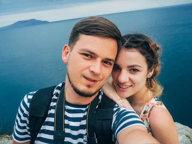 Счастливая влюбленная пара и ее парень делают селфи в поездке на отдых на море