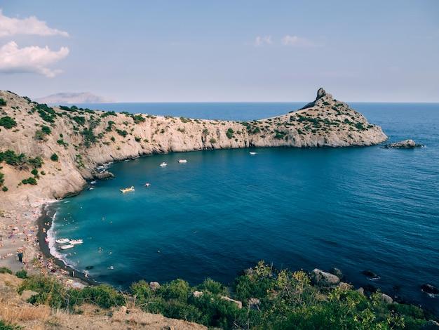 Пейзаж с морем и горами и пляжем под голубым небом летом в крыму