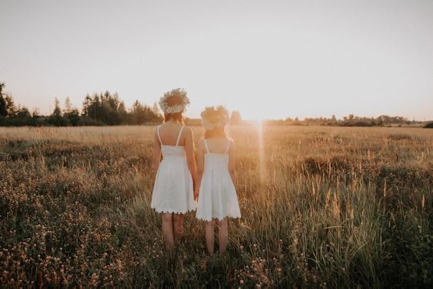 母と娘は夏に戻って白いドレスと花の花輪の分野で日没に立つ