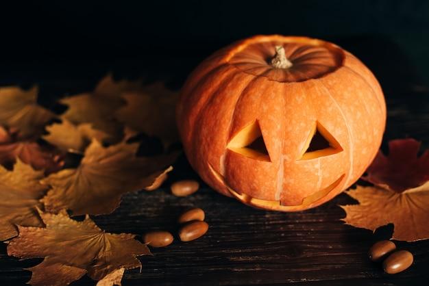 秋のオレンジ色のカエデの葉とドングリのハロウィーンのお祝いのジャックランタンカボチャ