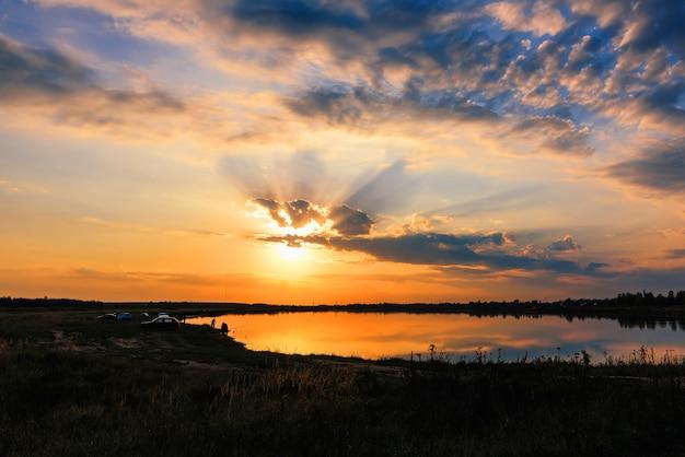 漁師釣りのシルエットと湖の秋のカラフルな夕日