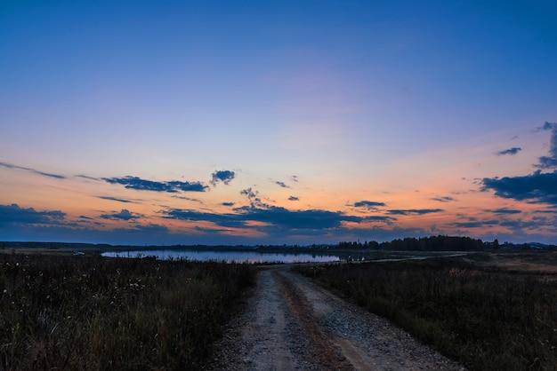 秋の夜の夕暮れ時の湖と道路のある風景