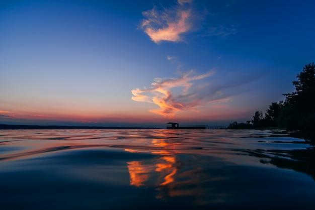 海の水の波の美しい反射と赤青の夕日
