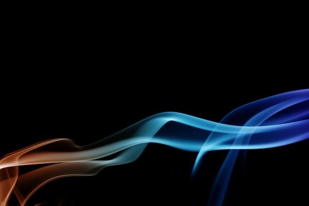 波と黒の背景にさまざまな色の煙