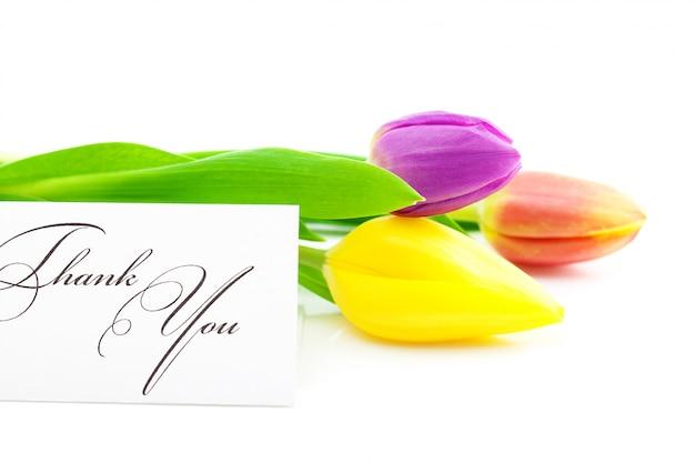 Красочные тюльпаны и карточка с надписью спасибо, изолированные на белом