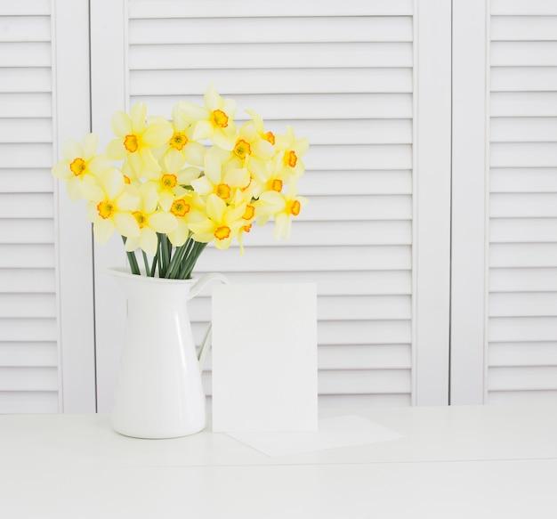 白いシャッターの上の花瓶に黄色い水仙の花のクローズアップ。きれいなプロヴァンス風の装飾